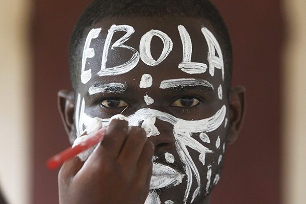 An actor prepares before a performance during an awareness campaign against Ebola at Anono school in Abidjan